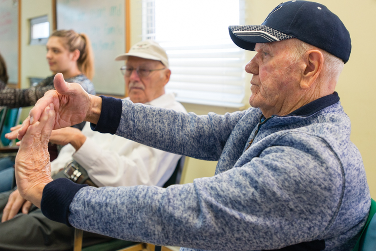 Tracy Williams, 80, stretches during the morning exercises at the WISE & Healthy Aging adult day service center. Williams, retired from the Air Force, said he enjoys when the college students visit the adult day service center visit. (Heidi de Marco/KHN)