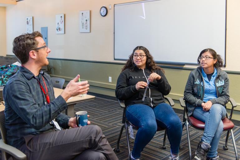 Eric Waters, coordinador para el programa de salud del comportamiento en Life Academy High School lidera una discusión con Fernanda May, de 17 años, y Graciela Pérez, de 17, en La Clínica de la Raza en Oakland, California, que provee entrenamiento en primeros auxilios y prácticas a estudiantes en organizaciones de salud mental. (Heidi de Marco/KHN)