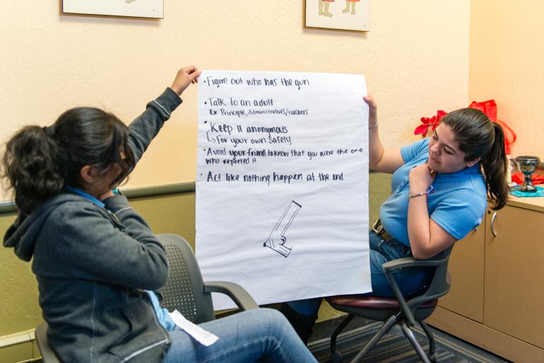 Graciela Pérez, de 17 años, y Nayely Espinoza, de 17, sostienen su asignación grupal durante una presentación en clase. Los estudiantes se preparan para sus prácticas de salud mental (Heidi de Marco/KHN)