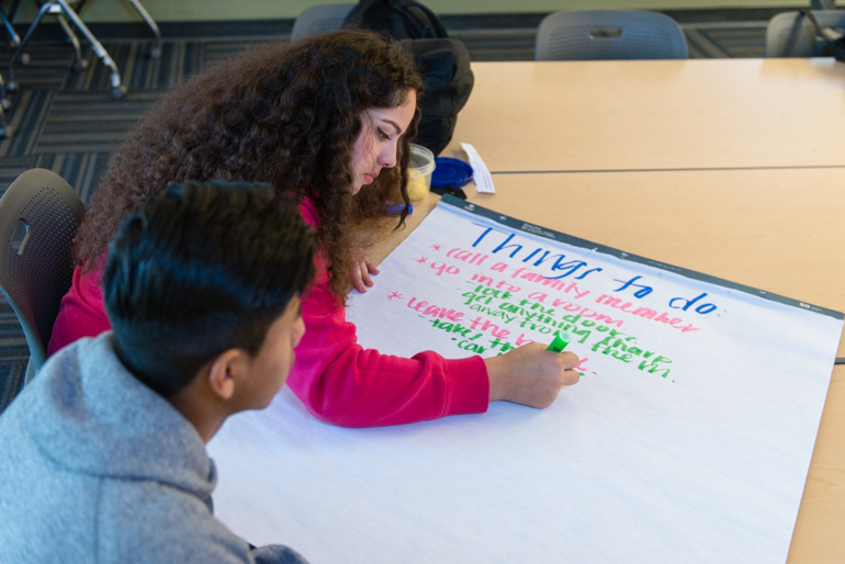 Elizabeth Ochoa, de 17 años, y Víctor Ramírez, de 17, trabajan en una tarea durante el entrenamiento en salud del comportamiento. Los estudiantes de East Oakland caminan al centro desde la escuela. (Heidi de Marco/KHN)