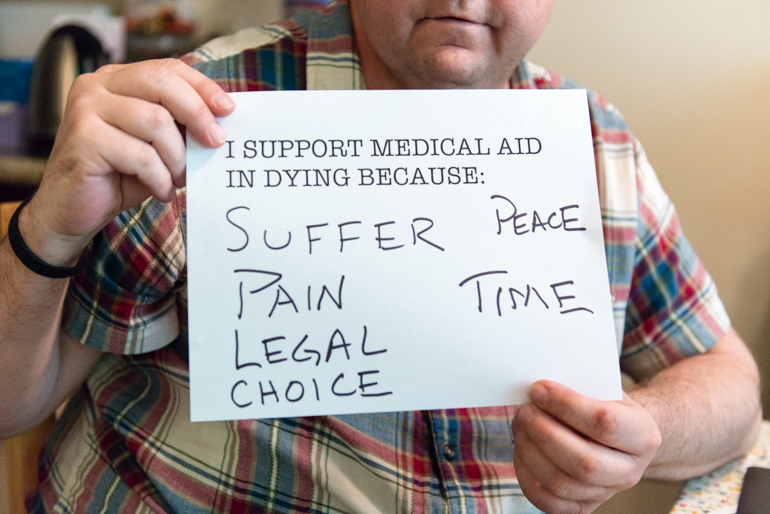 Fairchild holds a sign showing why he supports medical aid in dying. The 46-year-old Burbank resident wants to have the right to die if the pain from his melanoma becomes unbearable. (Heidi de Marco/KHN)