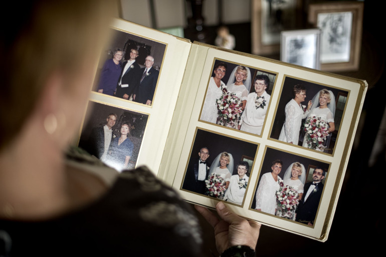Kristin Sigg looks at wedding photos that include her mother. (Travis Young/Austin Walsh Studio for KHN)