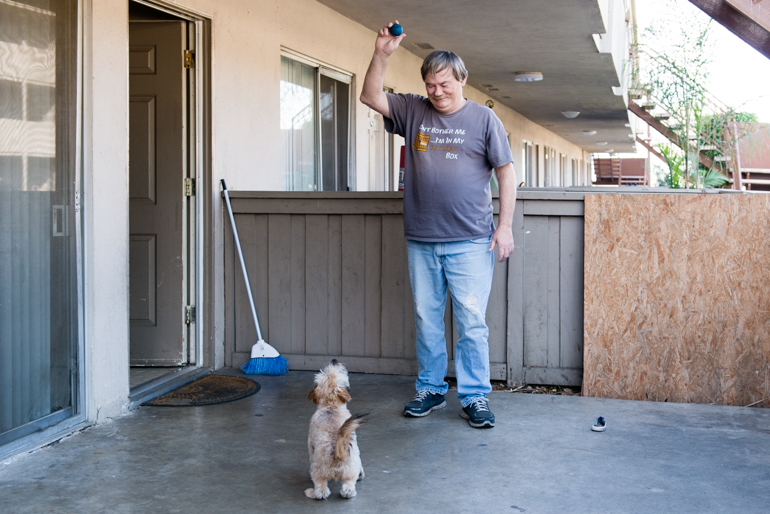 "Meade plays with his puppy Scrappy in his apartment patio. ""If I lost this apartment, I would give Scrappy to my neighbors…I wouldn't want him to be stressed out living in the streets.""(Heidi de Marco/California Healthline)"