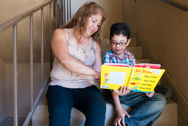 Torres reads to her U.S. born son Esau Rodriguez, 7, on the stairs of their apartment. DAPA, or Deferred Action for Parents of Americans and Lawful Permanent Residents, would allow undocumented adults like Torres to seek protection from deportation if they lived in the country continuously since 2010 and had a U.S. born child. (Heidi de Marco/CHL)