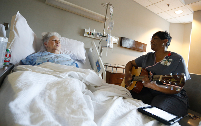 Queze Ferguson, 75, listens to music therapist Angela Howard sing and play the guitar. Ferguson was hospitalized in the geriatric unit of UAB Hospital-Highlands. (Hal Yeager for California Healthline)