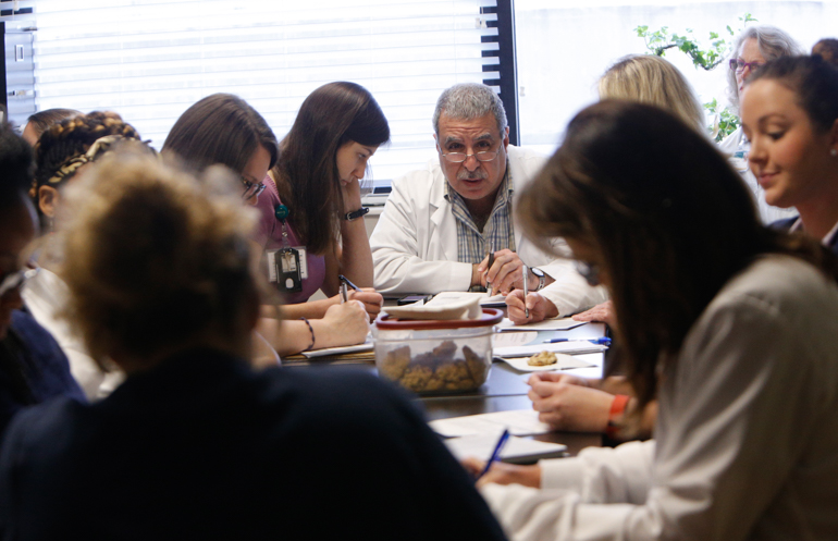 A team of medical professionals gather for a daily meeting to discuss the elderly patients at the Acute Care for Elders, or ACE, unit at UAB Hospital-Highlands. (Hal Yeager for California Healthline)