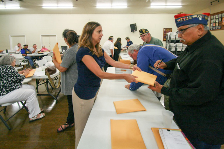 Meghan Callahan hands out envelopes of No on 61 campaign materials to veterans at a Sacramento Veterans Affiliated Council meeting on Sept. 1, 2016. Callahan works for a media relations firm paid by the campaign, which has received more than $86 million dollars from pharmaceutical companies. (Pauline Bartolone/California Healthline)