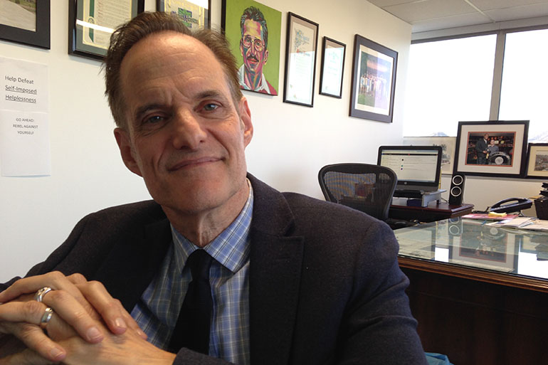Michael Weinstein, president of the AIDS Healthcare Foundation, in his office in Los Angeles. Behind him is a painting of Chris Brownlie, who worked with Weinstein to found the first AIDS hospice in LA. He is backing Propositions 60 and 61. (April Dembosky/KQED)