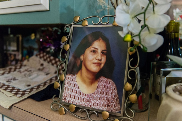 "A photograph of Rosemary Navarro's mother, Rosa Maria Navarro, sits on her dining room table. Navarro's mother died in 2009 from Alzheimer's disease. ""What I went through with my mom I wouldn't wish on anyone,"" Navarro said. (Heidi de Marco/KHN)"