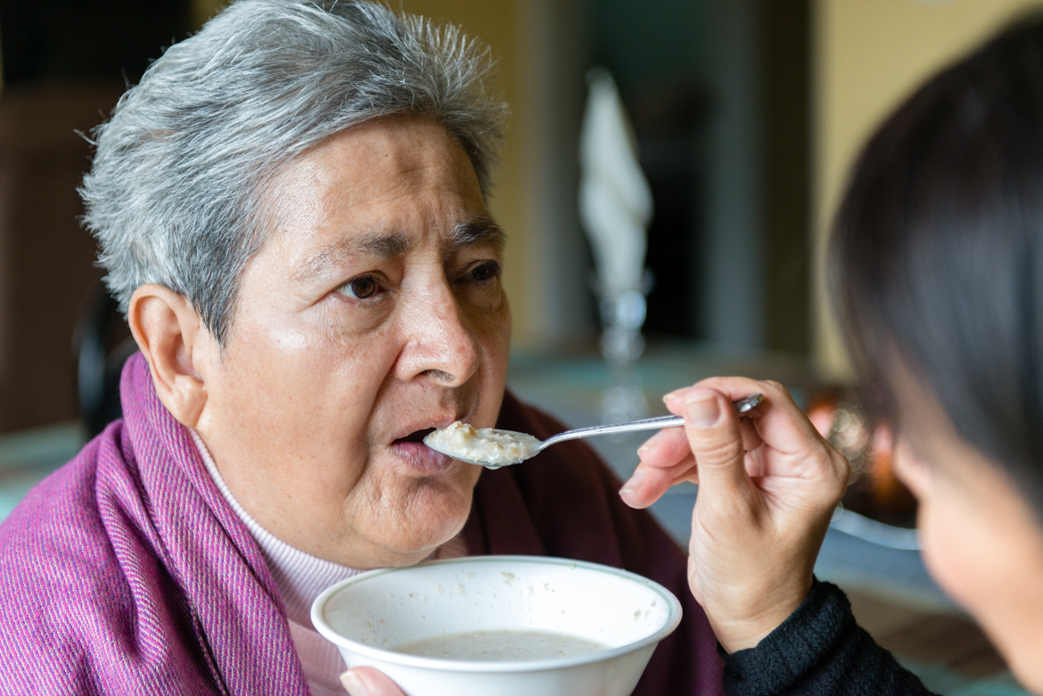 "Tania Yanes feeds oatmeal to her mother, Blanca Rosa Rivera. ""My mom is 100 percent dependent on us."" says Yanes. (Heidi de Marco/California Healthline)"