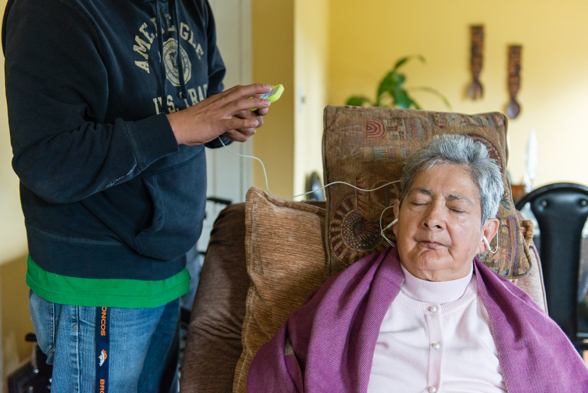 Mario Yanes, 48, uses an IPOD to play music for his mother, Blanca Rose Rivera. (Heidi de Marco/California Healthline)