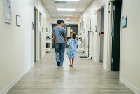 Nurse walking with girl in hospital corridor