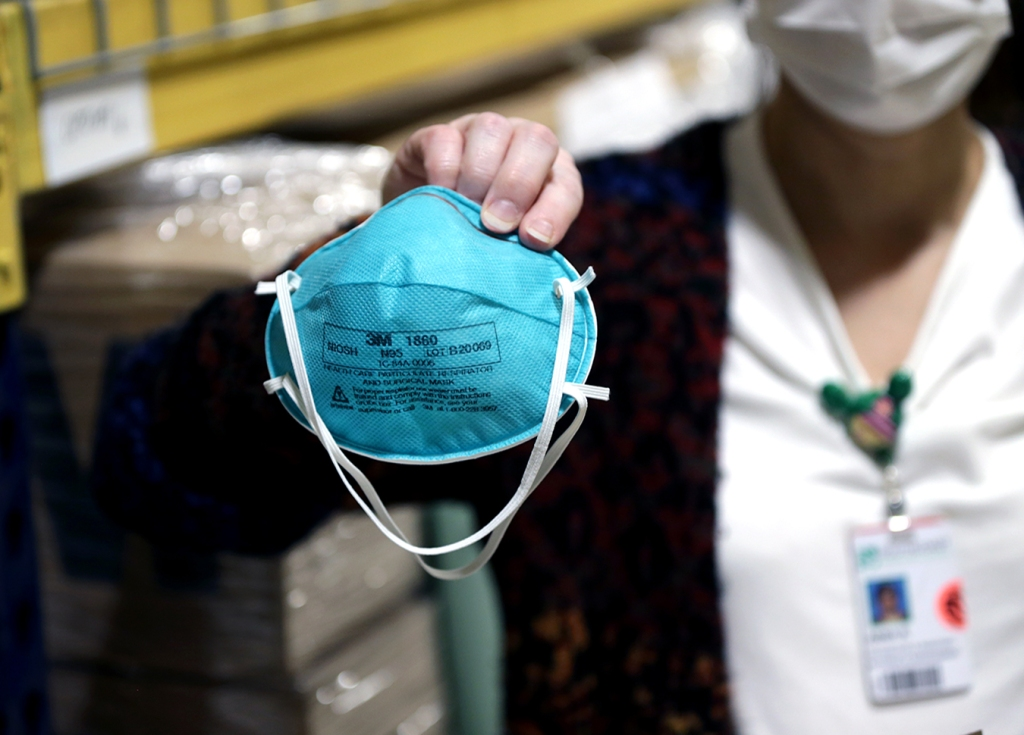A masked woman holds an N95 mask