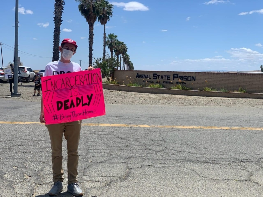 "man holds bright pink sign protesting covid cases in prison. sign reads ""incarceration is deadly"""