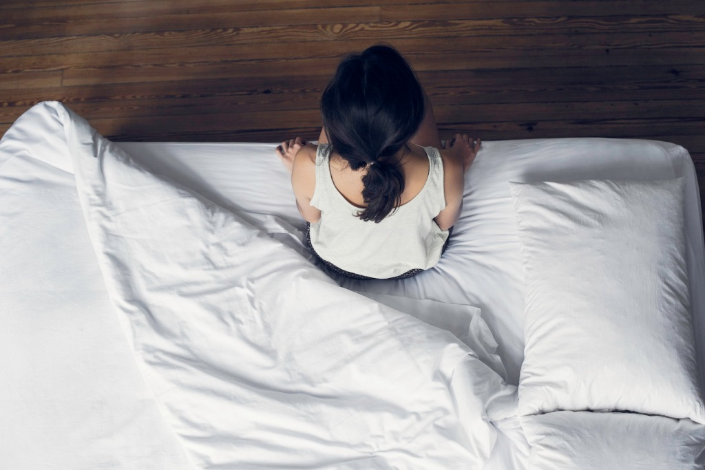 Woman sitting on edge of bed waking up
