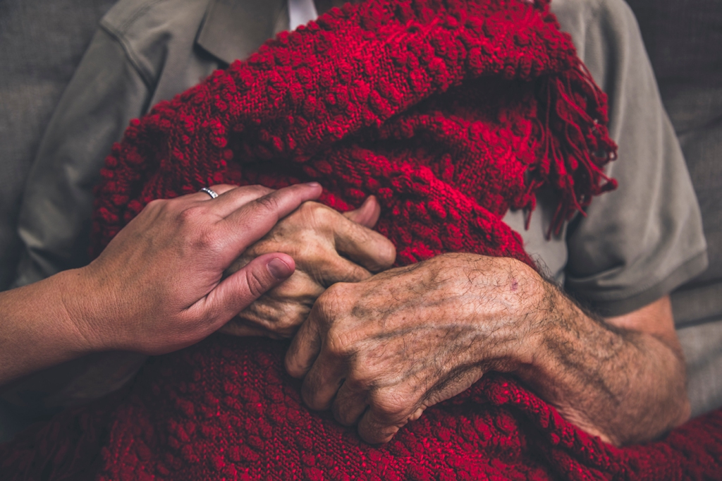 Someone holds the hand of a frail senior