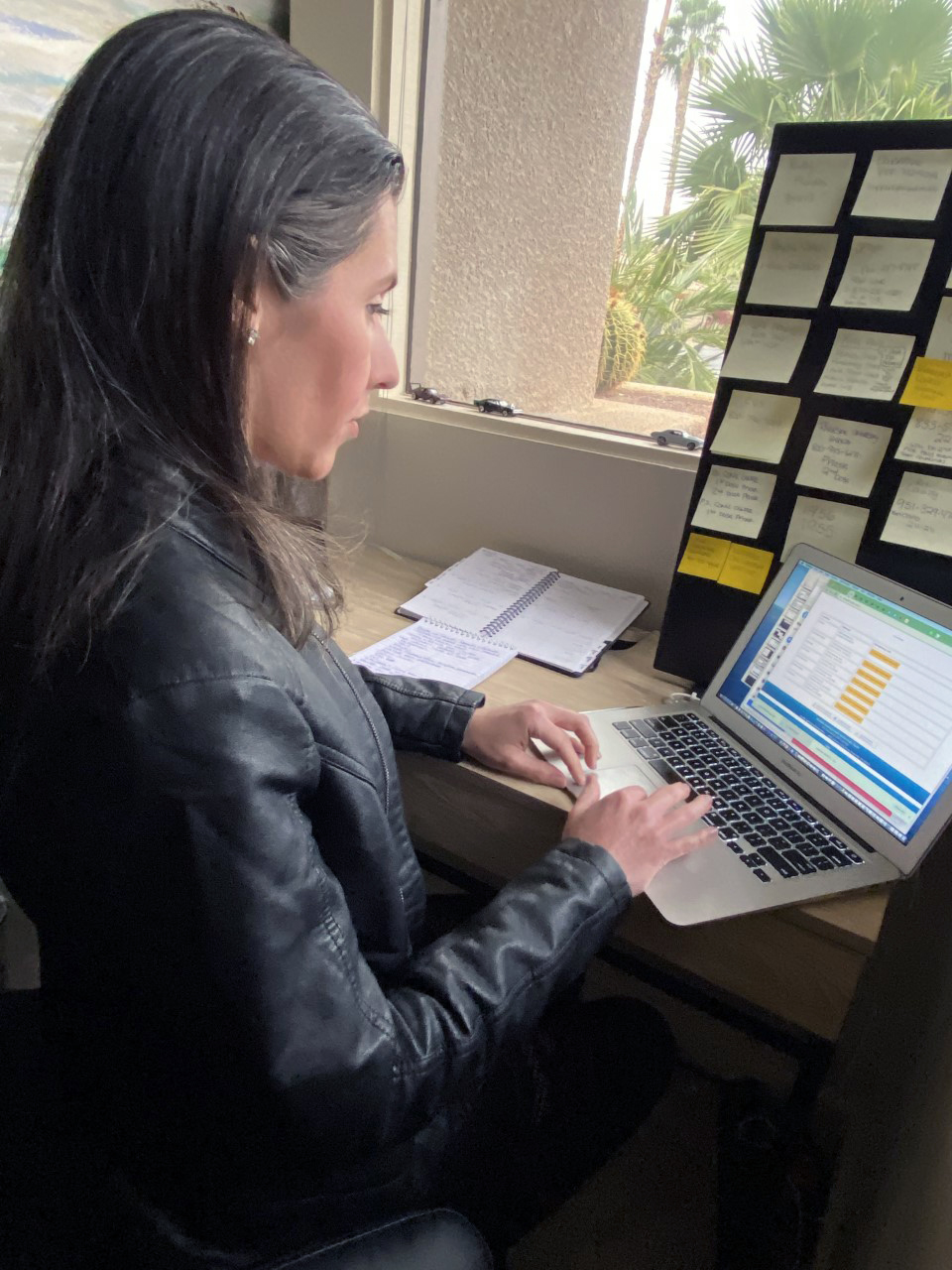 a woman sitting in front of a laptop