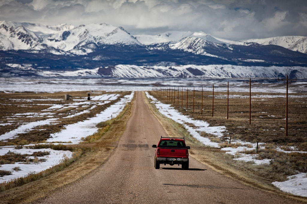 landscape of Walden, Colorado with a red truck on a rural road