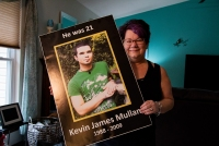 Kathi Arbini holds a poster with her son Kevin Mullane's photo