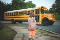 Rear view of schoolgirl with backpack waiting for bus while standing on footpath