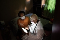 Doctor talking to senior female patient in a home visit